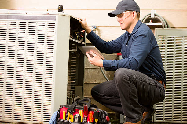 Repairmen works on a home's air conditioner unit outdoors. He is checking the compressor inside the unit using a digital tablet.  He wears a navy blue uniform and his safety glasses.  Tools inside toolbox on ground.
